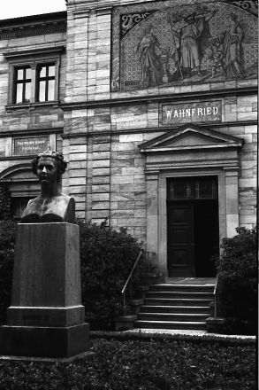 """Haus Wahnfried i augusti 2010. Gatufasaden med bysten av Richard Wagners mecenat, kung Ludvig II av Bayern. Över entrén en sgraffitto föreställande Wotan med sina två korpar, till vänster flankerad av """"Tragedin"""" i form av Wagners favoritsopran Schröder-Devrient, till höger av """"Musiken"""" i Cosimas gestalt med sonen Siegfried."""